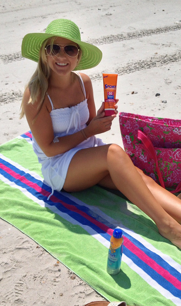 Mica at the beach with sunscreen and a hat.