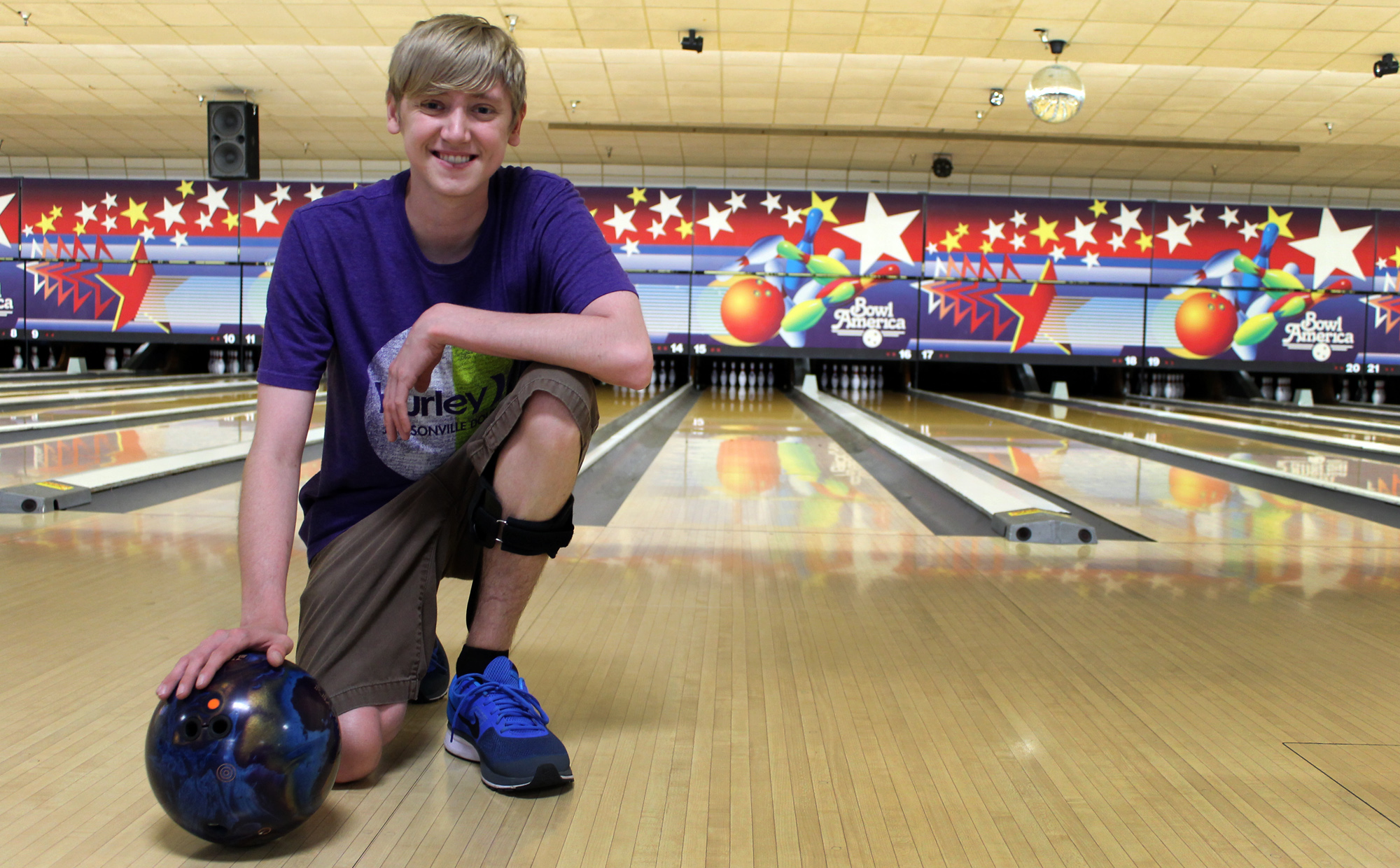 Curtis Higgons, 22 year-old double lung transplant recipient at Mayo Clinic in Florida poses at the bowling alley with his bowling ball.