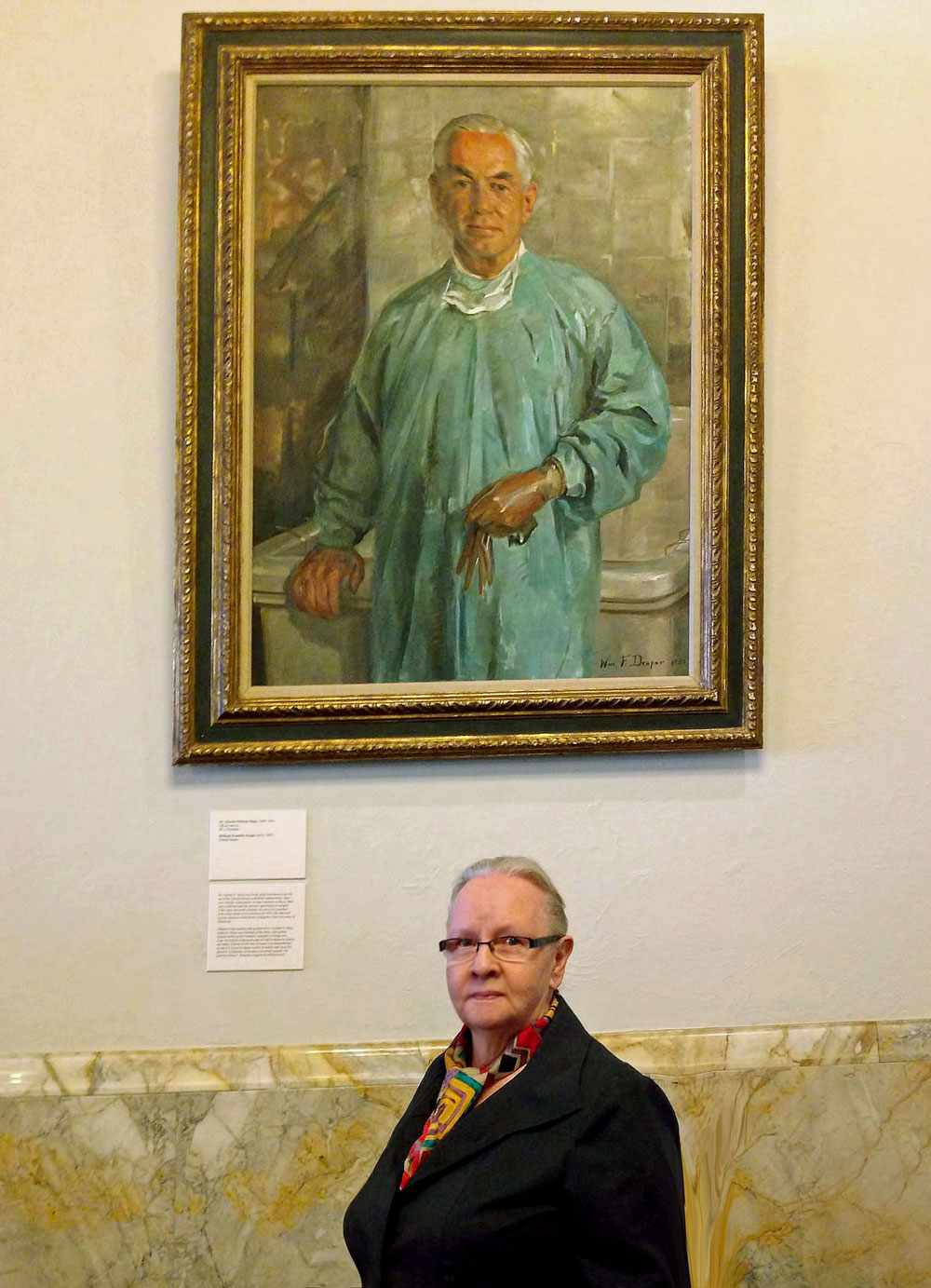 Elaine Stewart poses in front of a painting of Dr. Charles W. Mayo.