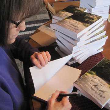 """Jenny Peterson signs copies of her book, """"She Walked by Faith, Not by Sight."""""""